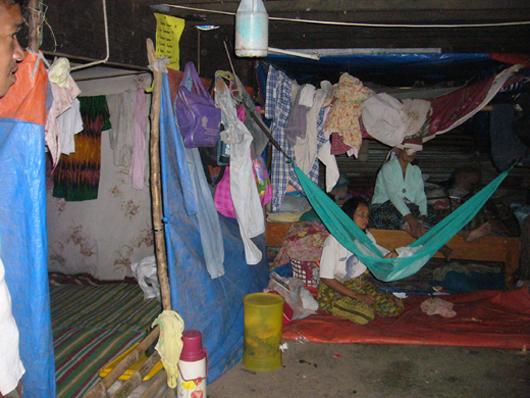 高床の体育館の下に間仕切りを作って生活する避難民 (2009年2月27日、ダトゥ・ピアン町)